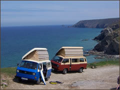 Two campervans with surfboard at cliff-top location